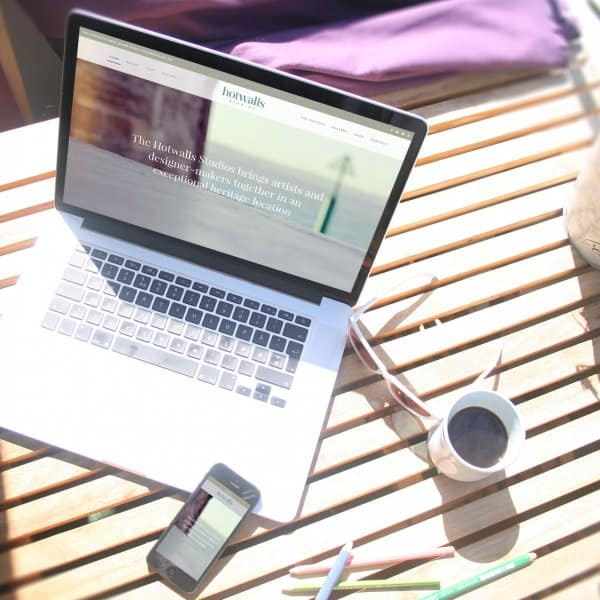 Hotwalls Studios, Portsmouth, website design, homepage on macbook and iphone, outside on a table in the sun