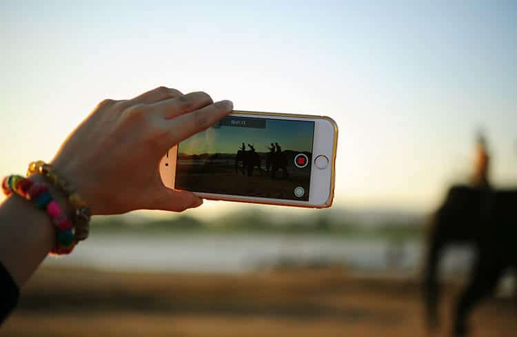 person holding their mobile phone which is videoing the landscape in front of them.